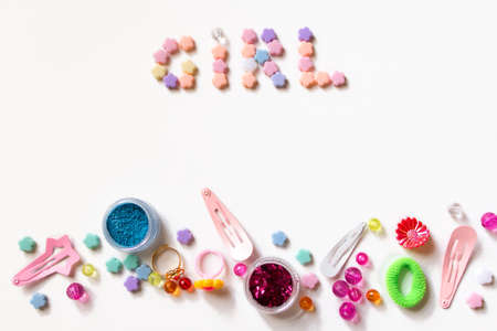 baby flower: Little girl accessories lifestyle set on  white background.  Many little girl accessories scattered on blank paper - beads, hair clips, eyeshadow. The inscription Girl is on the top of image Stock Photo