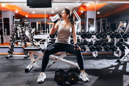 Athlète professionnel de musculation se détendre après l'entraînement épuisant. L'athlète se détendre et boire de l'eau de la bouteille de sport à l'intérieur de la salle de gym. Banque d'images - 54302299