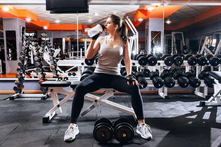 Professionele bodybuildersatleet ontspant na vermoeiende training. De atleet ontspant en drinkt water van sportfles in gymnastiekbinnenland. Stockfoto