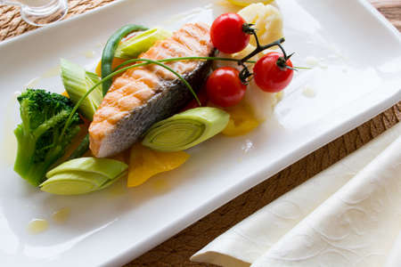 side dish: Steam salmon with a side dish of fresh vegetables on a white square plate. Top view Stock Photo