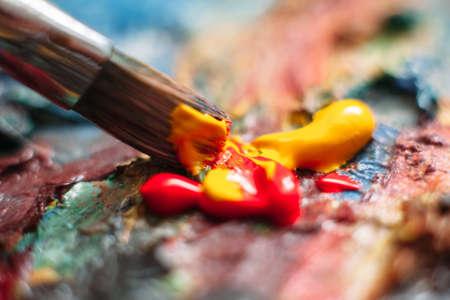 Peintre mêle peinture à l'huile jaune et rouge sur la palette. Gros plan du processus de mélange de peinture dans l'art en milieu de travail. Banque d'images - 55364908