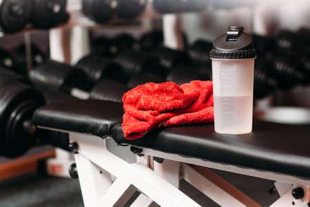 Sport, fitness, style de vie et de musculation sain concept - gros plan de la bouteille avec de l'eau et une serviette humide dans le gymnase de fond. Set de choses sport personnelle se trouvait sur la formation banc salle de fitness Banque d'images - 55364926