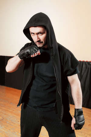 combative sport: Aggressive mid adult  street fighter in black sport cloth. Street fighter in training gloves staying in gym and looking at camera with threat.  Mid adult man healthy sport lifestyle concept. Stock Photo