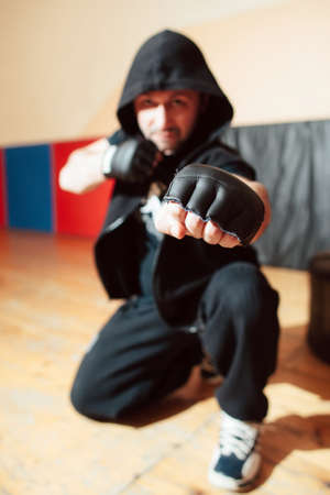 self defence: Aggressive mid adult street fighter in black hood ready to fight. Street fighter in training gloves shows his big fist. Man self defence lifestyle concept. Stock Photo