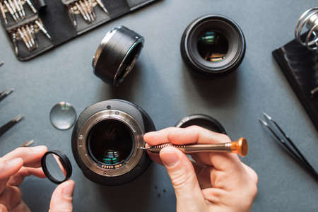 Photo camera lens repair set. Technician engineer check optics alignment and maintenance support of broken photographic 85 1.2 photo camera lens part. Pov to workplace and engineers hands.