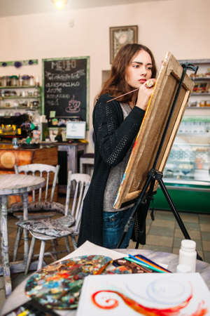 studious: Hipster artist paints a painting in defocused cafe interior. Closeup of painting process in light art workshop interior. Creative  studious hipster woman painter paints in her studio picture.