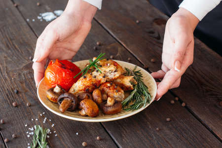 the shish kebab: Waiter serving a shish kebab with tomato and mushrooms on wooden background. Chief decorating food for presentation in small cafe. Waiter serving shish kebab with fresh vegetables for retail. Stock Photo