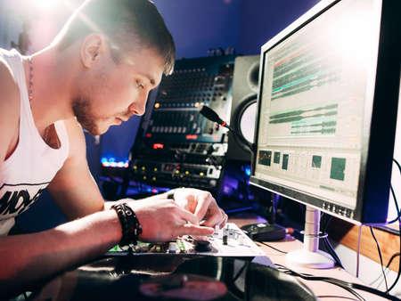 masters of rock: DJ adjusts equipment in the recording studio. DJ adjusts music equipment before starting work.  Composer checks sound panel .