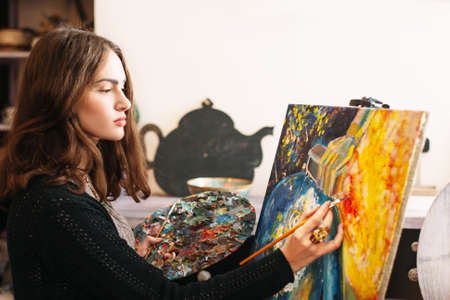 workroom: Creative pensive  painter paints a colorful picture. Creative process of creating abstract painting in art workroom. Closeup. Creative positive woman painter paints in her studio abstract picture. Stock Photo