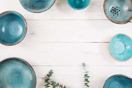 free plates: Many turquoise clay empty plates and free space in center on a white wooden background. Flat lay of set of trendy handmade empty plates. Organic food, healthy life, pottery, decoration concept