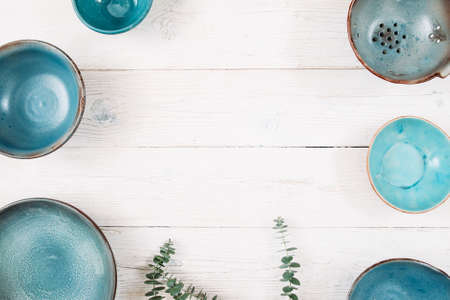 free plates: Many turquoise clay empty plates and free space in center on a white wooden background. Top view on set of trendy handmade empty plates. Organic food, healthy life, pottery, decoration concept