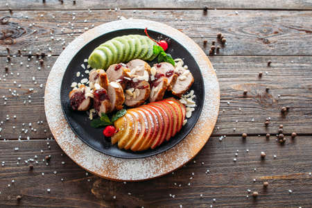 baked meat: Food photography of baked veal with fresh fruits on wooden background. Baked meat with tropical fruits top view. Flat lay of creative food from baked veal on wooden table. Stock Photo