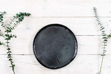 free dish: Top view empty black plate on rustic wooden table. Ceramic black plate on white wooden background with free space. Flat lay of handmade black dish on white wooden table. Stock Photo