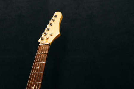 string top: Headstock of the six string electric guitar top view in sound recording studio. Headstock of electric guitar  flat lay on black background. Musical instrument closeup with free space. Stock Photo