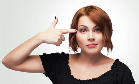 stupidity: Crazy woman. Young beautiful woman gesturing finger against her temple. Concept of  suicide, disapproval of offer or situation, stupidity, threat. Isolated on white. Stock Photo