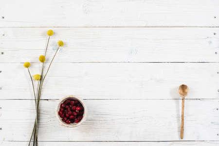 Obst Frühstück mit freiem Platz auf Holztisch. Getrocknete Früchte und Blüten mit Draufsicht. Diätetische Lebensmittel flach lag auf weißem Holz Hintergrund mit Kopie Raum.
