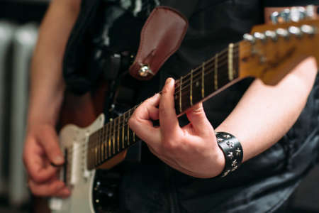 acoustical: Musician playing six string electric guitar in sound recording studio. Rocker playing on electric guitar, closeup. Musical instrument closeup.