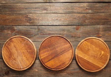 3 개의 빈 나무 피자 접시는 그림의 하단에 나무 테이블에 놓여 있습니다. 공간을 복사합니다. 수평선. 빈 나무 피자 접시의 평평한 누워