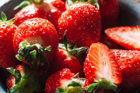wholes: Bunch of fresh strawberries halves and wholes. With green strawberry stalks. Fresh, tasty red strawberry, extreme close-up.