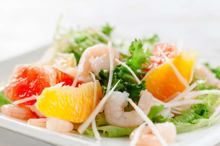 Fresh yummy shrimp salad with oranges and grapefruit  and cheese on the white dish. Close up. Top view of seafood salad with shrimp Imagens