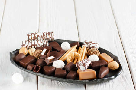 sorts: Assorted chocolate candies on black clay plate. White wooden background with free space on top. Different sorts of chocolate candies front view. Stock Photo