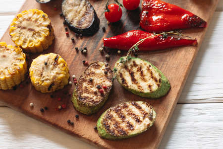 vegetable marrow: Delicious grilled vegetables on cutting board. Flat lay of close-up corn, pepper, vegetable marrow, eggplant on wooden background.
