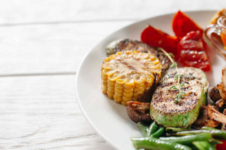 free space: Grilled vegetables on white plate. There is corn, tomato, mushrooms, asparagus and cabbage in vegetarian bbq. Free space on white table Stock Photo