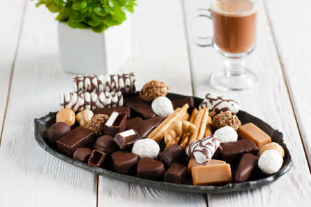 appetize: Delicious plate with different sweets on white wooden table with cappuccino. Chocolate candies and cookies on black plate. Close-up of chocolate candies set, front view, focus on foreground.