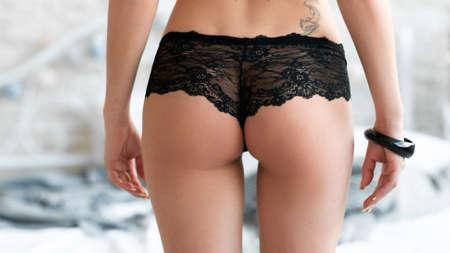 mujeres jovenes desnudas: Foto de detalle de la mujer nalgas en bragas de encaje negro. Primer extremo de la mujer atractiva culo. glúteos perfectos en ropa interior de encaje negro. Foto de archivo