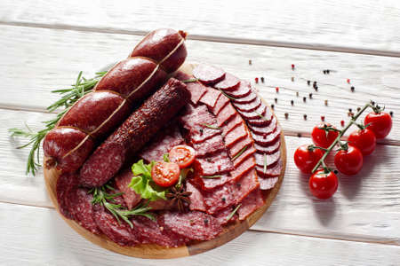 cold background: Cut salami mix on catering platter on white wooden background. Front view of salami mix plate. Wooden platter with different kinds of meat
