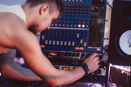 master volume: Composer adjusts a sound panel in the sound recording studio. DJ adjusts music equipment before starting work.  Sound engineer checks the sound panel. Digital sound equipment service concept