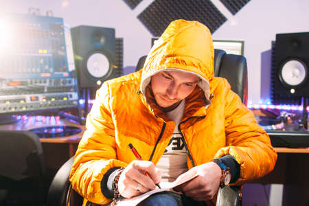 letras musicales: DJ writes new lyrics in recording studio. Young man in yellow coat wtites lyrics in recording studio.  DJ create new music track.