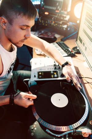 master volume: DJ creates composition in the recording studio.  DJ playing music in the recording studio. Studio record of new music track. Stock Photo