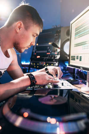 creates: DJ creates composition in the recording studio.  DJ playing music in the recording studio. Studio record of new music track. Stock Photo