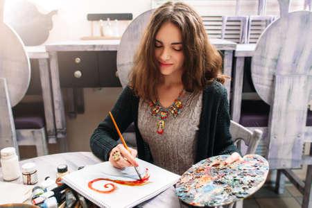 Mooie lachende jonge vrouw die een foto met plakkaatverf. Vooraanzicht op tekenen meisje met palet in haar hand. Lachende jonge vrouw een beeld te schetsen in de studio