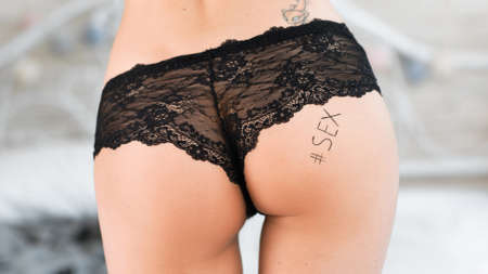 nude female buttocks: Closeup of female butt in beautiful black panties with text sex written on her butt. Extreme closeup of sexy butt with word. Erotic picture of female buttocks.
