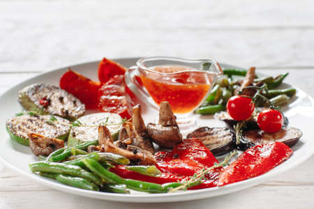 vegetable marrow: Grilled vegetables with red sauce on white plate. Front view on grilled asparagus, vegetable marrow, tomato, pepper, eggplant and mushrooms on white plate with cup of ketchup close-up