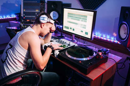 producer: Tired DJ after hard work in sound recording studio. Exhausted DJ after overtime, he has problems and headache. Tired sound producer hiding his eyes.