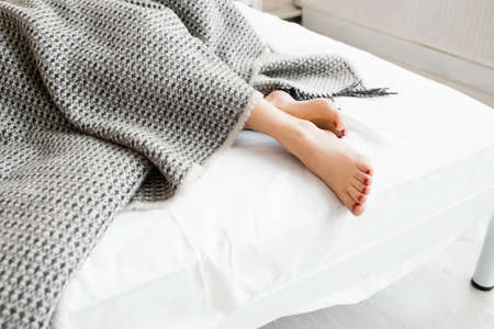 Woman feet under gray blanket sideview. Beautiful young woman feet with red pedicure on the bed. Sleeping woman legs under the gray blanket