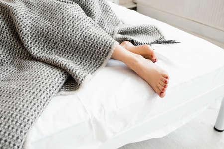 descansando: Pies de la mujer bajo el sideview manta gris. Bellos pies de la mujer joven con pedicure rojo en la cama. Dormir piernas de la mujer bajo la manta gris