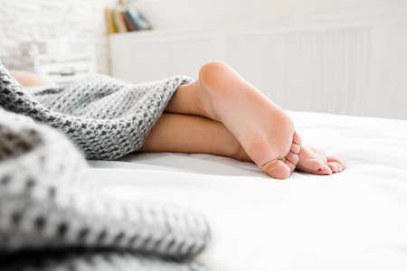 Slapende vrouw voeten onder deken. Mooie voeten van slapende vrouw onder de deken op haar bed. Slaapkamer op de achtergrond. Focus op mooie voeten. Vrije ruimte