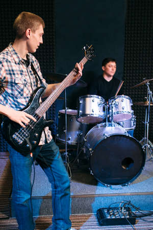 making music: Bass guitar player and drummer play music . Front view on two musicians, making music with bass guitar and drums at music studio. Music band at sound recording studio