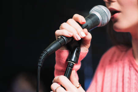 female singer: Microphone and unrecognizable female singer close up. Cropped image of female singer in pink dress , singing into a microphone, holding mic with two hands. Copyspace