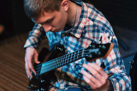 bass player: Musician tuning strings on his bass-guitar. Front view on bass player spinning guitar tuners. Closeup on young guy with bass guitar Stock Photo