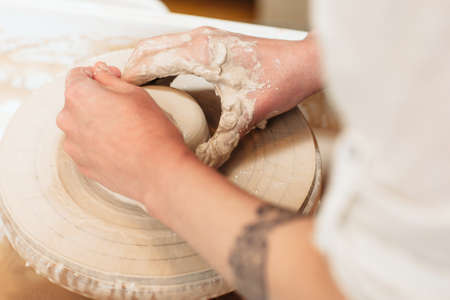 shaping: Potter hands shaping clay top view. Closeup on artisan hands making pottery. Art therapy process Stock Photo