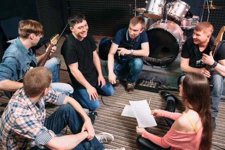 lifestile: Musicians learning new song on the floor. Top view on music band members sitting on the floor with song text. Vocalist smiling at woman. Lifestile of young people group. Teamwork.