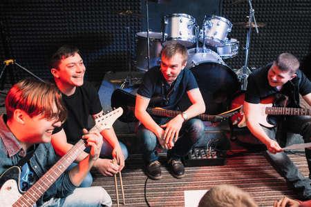 Rire musiciens heureux assis avec des instruments au studio. Guitaristes et le batteur discuter d'une plaisanterie. Rehearsing de plaisir Banque d'images - 58961695