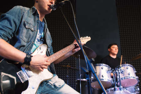 vocalist: Playing on guitar vocalist and drummer on background. Focus on guitar player singing into the micriphone, playing drummer on background. Student music band on stage