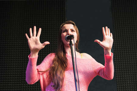 woman hands up: Women performing against the microphone. Emotionally talking into the microphone young beautiful woman in pink dress. Hands rised up in protest