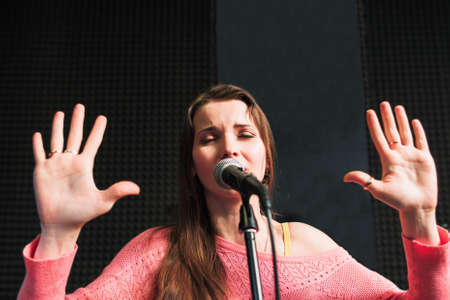 emotionally: Emotionally singing young girl with closed eyes and rised palms. Protesting woman in pink dress near the microphone.